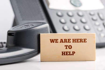 Soutien à la clientèle Simple Concept Design-Gros plan de petit morceau de bois avec Nous sommes ici pour aider Textes au bureau de l'opérateur de service client avec téléphone.
