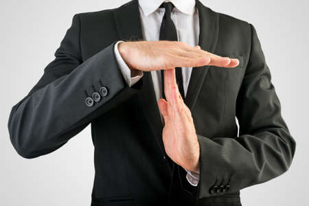 the end of time: Close up Businessman in Black Suit Showing Time Out Sign, Isolated on Gray Background.
