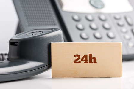 24h: 24h business telephone support concept with a small wooden sign saying - 24h - standing alongside a landline telephone instrument with the receiver off the hook in a close up view.
