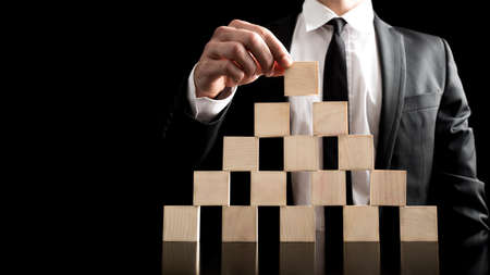 Close Businessman Arranging Small Wooden Plain Blocks to a Pyramid Figure on Black Background. An Imaginative Business Hierarchy Concept. photo