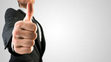 emphasizing: Businessman in Black Suit Showing Thumbs Up Sign, Emphasizing Approval or Satisfaction, in Close Up. Isolated on Gray Background.