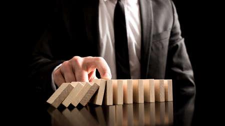 テーブルの上に小さな木のブロックからドミノ効果を停止する実業家。問題を解決するための創造的な概念。