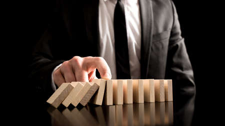 stop: Businessman Stopping the Domino Effect from Small Wooden Blocks on the Table. A Creative Concept for Solution to Problem.