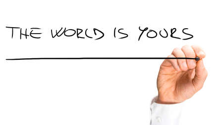 Close up Human Hand Writing Underlined The World is Yours Texts on White Background. A Simple Business Concept Design. photo