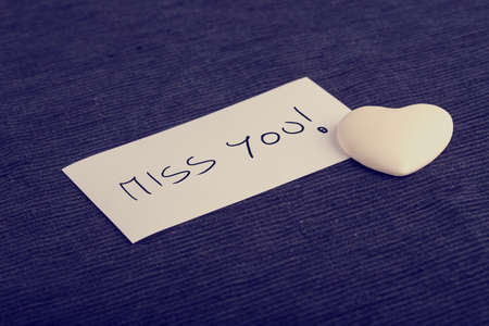 Miss You concept with a small white heart and handwritten card lying on a blue background at an oblique angle symbolic of tenderness and love.