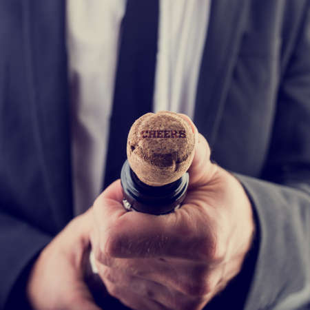 Retro Image of Businessman Opening Wine Bottle with Cheers Texts on Bottle Cover. photo