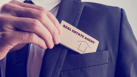 and real estate: Real Estate Agent in Black Suit Putting Small Wooden Piece with Real Estate Agent Text and Graphic to Front Pocket.