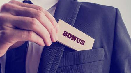 Close up Businessman in Black Suit Putting Small Wooden Piece with Bonus Text to Front Pocket. A Simple Company Bonus Concept. Foto de archivo