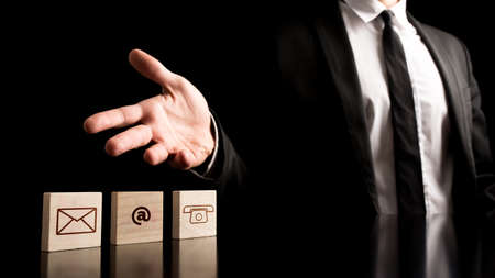 contact icons: Businessman Showing Contact Icons on Small Wooden Pieces on Table. Isolated on Black Background.