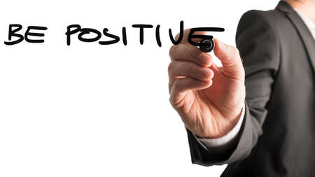 be the change: Businessman writing - Be Positive - with a black marker pen on a virtual screen over white with plenty of copyspace in an inspirational concept.