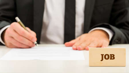 Close up Job Text on Small Wooden Piece in Front Businessman while Writing on White Table. A Simple Job Concept. photo
