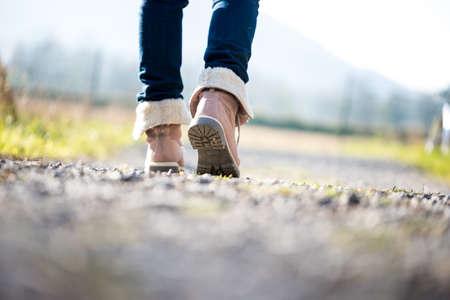 카메라에서 멀리 시골 길을 산책 청바지와 발목 높은 가죽 부츠에있는 여자의 다리의 얕은 DOF와 낮은 각도 지상보기. 스톡 콘텐츠