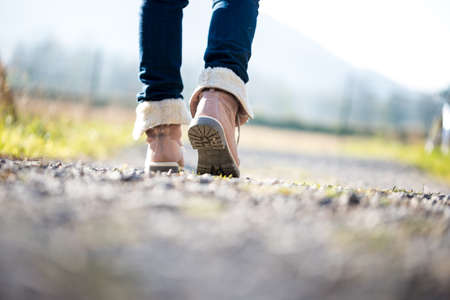 europe closeup: Low angle ground level view with shallow dof of the feet of a woman in jeans and ankle high leather boots walking along a rural path away from the camera.