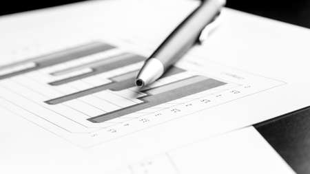 Stylish silver ballpoint pen lying on a bar graph at an oblique angle in a business analysis concept. photo