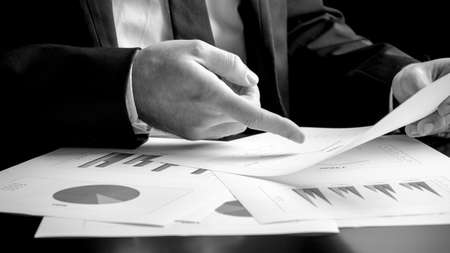 Businessman analysing a set of bar, pie and triangular graphs as he sits at his desk pointing to one document he is holding, close up greyscale in a business analysis, projections and strategy concept photo