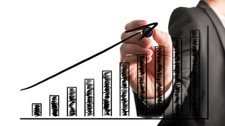 Businessman drawing an ascending bar graph with a black marker pen on a virtual interface over a white background during a presentation or planning meeting. photo