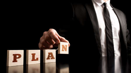 tactic: Simple Business Plan Concept - Businessman Arranging Small Wooden Blocks with PLAN Letters on a Pure Black Background. Stock Photo