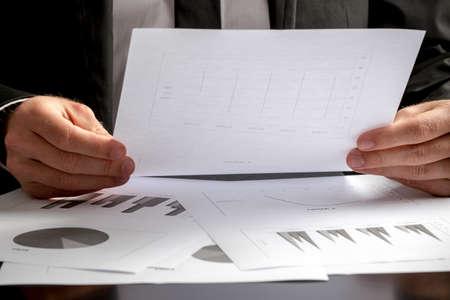 hoja de calculo: Close up de las manos de un hombre de negocios sentado en su escritorio el análisis de un conjunto de gráficos y la celebración de una hoja de cálculo con las estadísticas en la mano. Foto de archivo