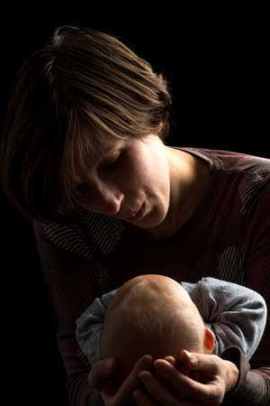 devotions: Dark portrait of a loving mother cradling her newborn baby tenderly in her arms as she looks down at it with love and devotion.