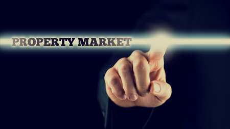 press agent: Retro image of a male hand activating a Property market button on virtual screen. Stock Photo