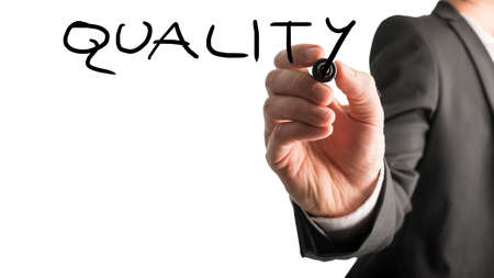 Male hand writing Quality on virtual whiteboard. Isolated over white background.