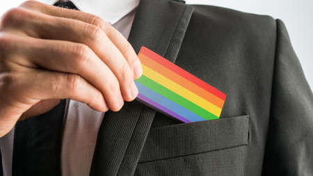 lgbt: Man withdrawing a wooden card painted as the gay pride flag from his suit pocket, close up of his hand.