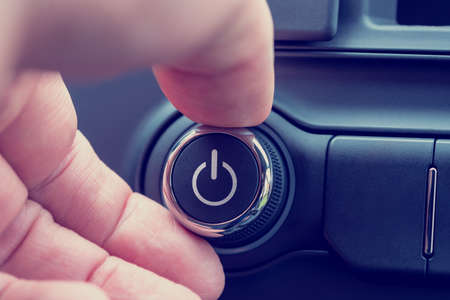 powerbutton: Close up of the fingers of a man turning onoff a power button with the power icon in white on a piece of electronic equipment. Stock Photo