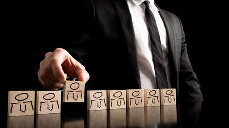 Businessman in black and white business suit arranging wooden pieces with people drawings on the table with pure black background. Simple human resource concept.