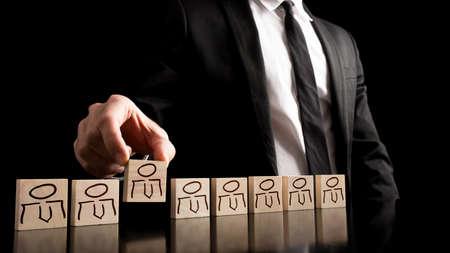 lideres: Hombre de negocios en traje de negocios en blanco y negro la organización de piezas de madera con las personas dibujos sobre la mesa con el fondo negro puro. Concepto simple de los recursos humanos.
