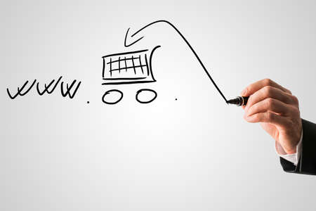 Online shopping and e-commerce concept with a businessman drawing a shopping cart in a www web address on a virtual interface with copyspace. photo