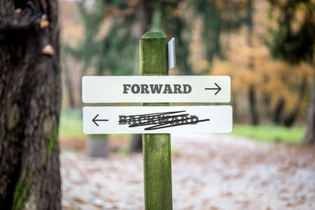 backward: Rural signboard with two signs saying - Forward - Backward - pointing in opposite directions with the sign saying Backward scribbled through and an arrow pointing to the route forwards to success.