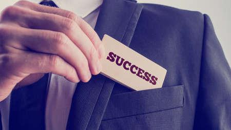 exito: Exitoso hombre de negocios que muestra una lectura de la tarjeta de madera - �xito - como �l la retira del bolsillo de su chaqueta, close up de la mano con retro desvaneci� efecto de filtro.