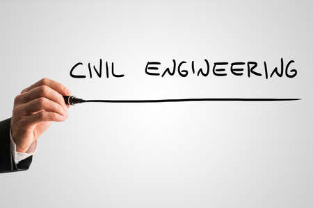 structural: Man writing the words Civil engineering with a black marker pen from behind a virtual screen or interface on a light grey background with copyspace, close up view of the text and his hand. Stock Photo