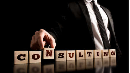 Consultant in Black Business Suit Arranging Small Wooden Pieces with ConsultingText on Black Background.