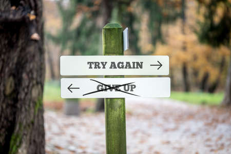give up: Signboard with two signs saying - Try again - Give up - pointing in opposite directions with the sign saying Give up scribbled through.