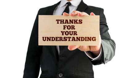 gratefulness: El hombre de negocios con un cartel en la mano la lectura - Gracias por su comprensi�n - en reconocimiento de clientes de pie por el negocio en tiempos de estr�s o durante la resoluci�n de problemas o interrupciones.