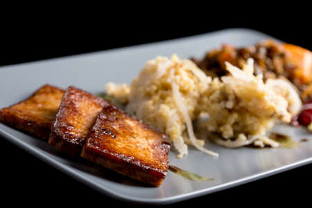 macrobiotic: Healthy homemade macrobiotic lunch made of marinated tofu, millet with sour turnip and oven baked vegetables.