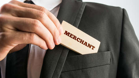 merchant: Man removing a small rectangular wooden sign saying Merchant from the pocket of his suit jacket.