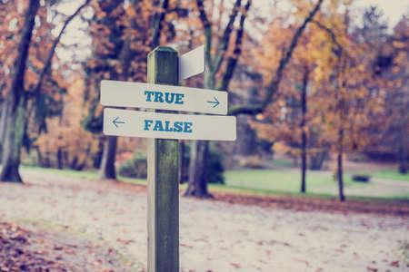 Drogowskaz w parku lub w zalesionej okolicy z strzałki skierowane w dwóch przeciwnych kierunkach wobec Prawda i fałsz. Zdjęcie Seryjne