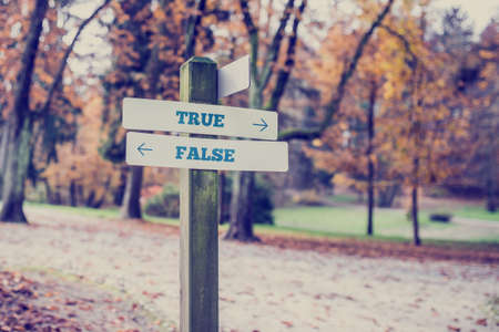 Poste indicador en un área del parque o boscosa con flechas que apuntan hacia dos direcciones opuestas Verdadero y Falso. Foto de archivo