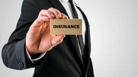 agent de sécurité: Gros plan de l'agent d'assurance tenant un petit panneau en bois rectangulaire disant assurance. Isolé sur fond gris.