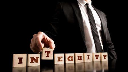 Close-up van de zakenman Het regelen Kleine Houten Stukken met Integriteit letters op zwarte achtergrond. Stockfoto