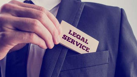 abogado: Empresario de retirar una tarjeta de madera lectura servicio legal del bolsillo de su chaqueta, efecto vintage en tonos imagen.