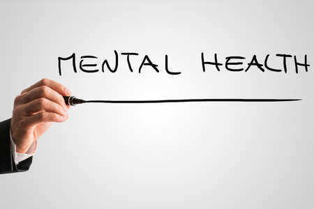mental health problems: Hand of a man writing Mental health on a virtual screen or interface with a marker pen with copyspace below.
