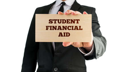 financial aid: Close up of businessman holding a rectangular wooden sign saying Student financial aid. Isolated on white background. Stock Photo