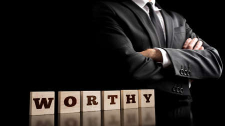 principled: Worthy Letters on Arrange Small Wooden Pieces with Confident Businessman Crossing Arms in Front of the Body. Captured on Black Background.