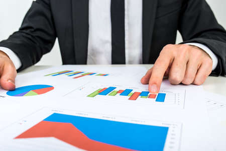 Businessman analysing a set of bar graphs as he sits at his desk pointing to one column chart, in a business analysis, projections and strategy concept. photo