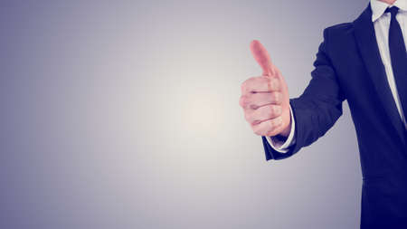 thumbs: Retro effect faded and toned image of a businessman giving a thumbs up gesture of approval and success,  with plenty of copyspace in a business motivation concept.