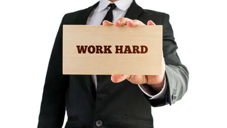 hardworking: Close up of businessman holding a wooden sign saying Work hard. Isolated on white background. Stock Photo