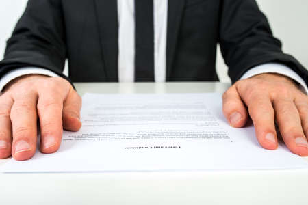 terms: Close up low angle view of the hands of a businessman reading a document or contract resting on either side of the page with focus to the text Terms and Conditions.